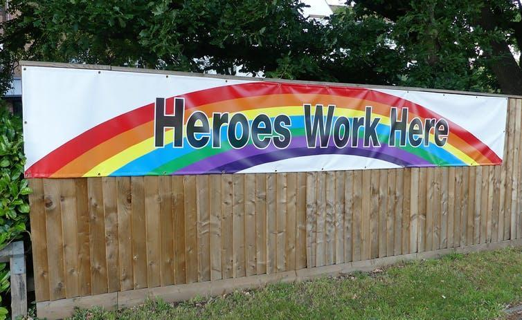 The fence of a care home with a banner saying 'Heroes Work Here' against a rainbow.