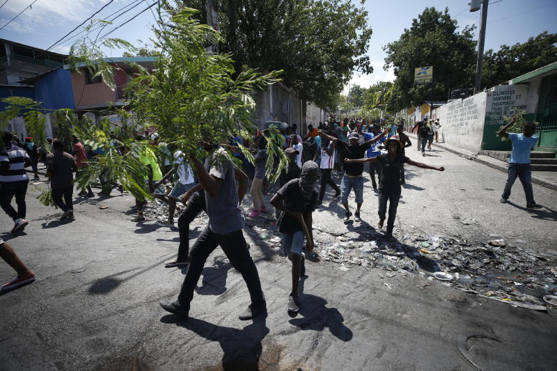 Haitians respond to a nationwide push to block streets and paralyze Haiti's economy as they press for President Jovenel Moise to give up power, in Port-au-Prince, Haiti, Monday, Sept. 30, 2019. Opposition leaders and supporters say they are angry about public corruption, spiraling inflation and a dwindling supply of gasoline that has forced many gas stations in the capital to close as suppliers demand the cash-strapped government pay them more than $100 million owed. (AP Photo/Rebecca Blackwell)