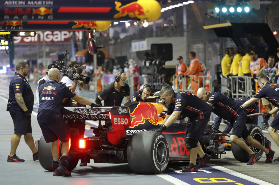 The crew for Red Bull driver Max Verstappen of the Netherlands push his car in pit lane during the first practice session at the Marina Bay City Circuit ahead of the Singapore Formula One Grand Prix in Singapore, Friday, Sept. 20, 2019. (AP Photo/Vincent Thian)