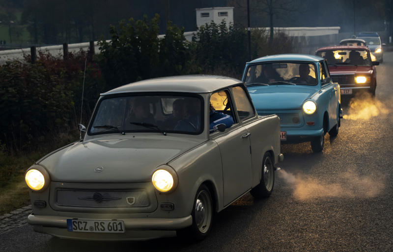 The legendary GDR Trabant (Trabi) cars drive along,  during a symbolic wall opening, celebrating the 30th anniversary of the falling wall in the outdoor area of the German-German museum in Moedlareuth, Germany, Saturday, Nov. 9, 2019. Moedlareuth, named 'Little Berlin', was the symbol of a divided village along the borderline between East and West Germany. The border ran straight through the little village. (AP Photo/Jens Meyer)