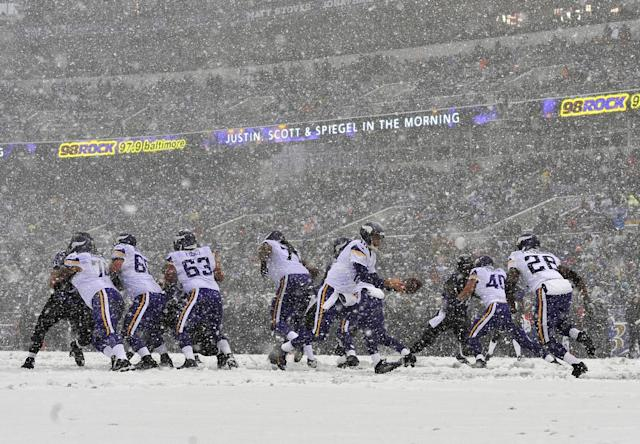 Snow falls as Minnesota Vikings quarterback Matt Cassel, center, prepares to hand the ball off to running back Adrian Peterson (28) in the first half of an NFL football game against the Baltimore Ravens, Sunday, Dec. 8, 2013, in Baltimore. (AP Photo/Gail Burton)