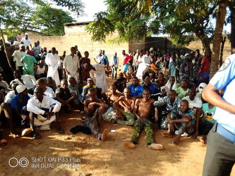 People sit on the ground after being freed by police from an Islamic rehabilitation centre in Ibadan