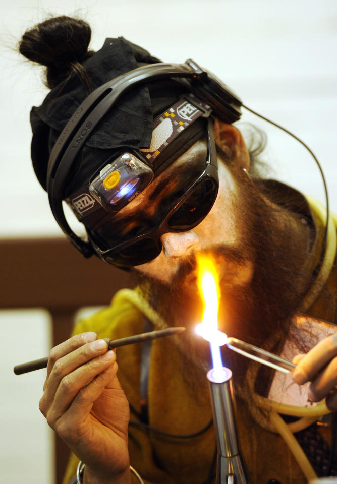 Drew Hsu, of Fort Collins, does torch work, a method of working with glass at the Denver County Fair Freak Show in Denver on Thursday, July 28, 2011. (AP Photo/Chris Schneider)