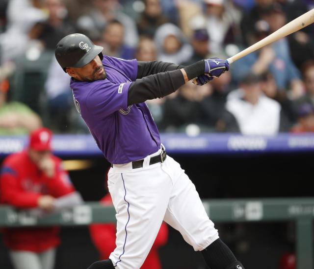Colorado Rockies' Ian Desmond follows through with his swing after connecting for an RBI-single off Philadelphia Phillies starting pitcher Jerad Eickhoff in the sixth inning of a baseball game Sunday, April 21, 2019, in Denver. (AP Photo/David Zalubowski)