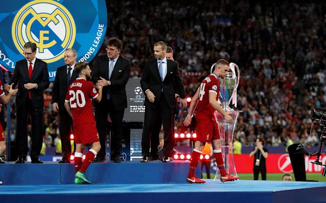 Soccer Football - Champions League Final - Real Madrid v Liverpool - NSC Olympic Stadium, Kiev, Ukraine - May 26, 2018 Liverpool's Adam Lallana and Jordan Henderson look dejected as they are awarded their runners up medals by UEFA president Aleksander Ceferin REUTERS/Andrew Boyers