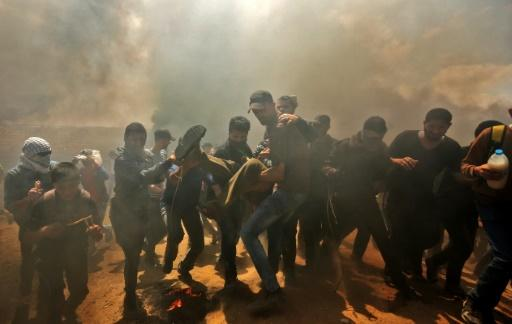 Palestinians carry a demonstrator injured during clashes with Israeli forces near the Gaza-Israel border on May 14, 2018