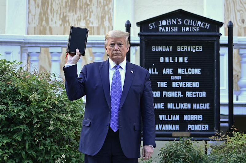 US President Donald Trump holds up a Bible outside of St John's Episcopal church across Lafayette Park in Washington, DC on 1 June 2020 (AFP via Getty Images)