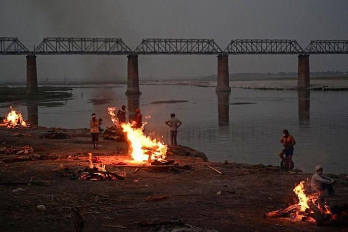 Funeral pyres are lit by the Ganges in Allahabad, where bodies have been washing downstream for days