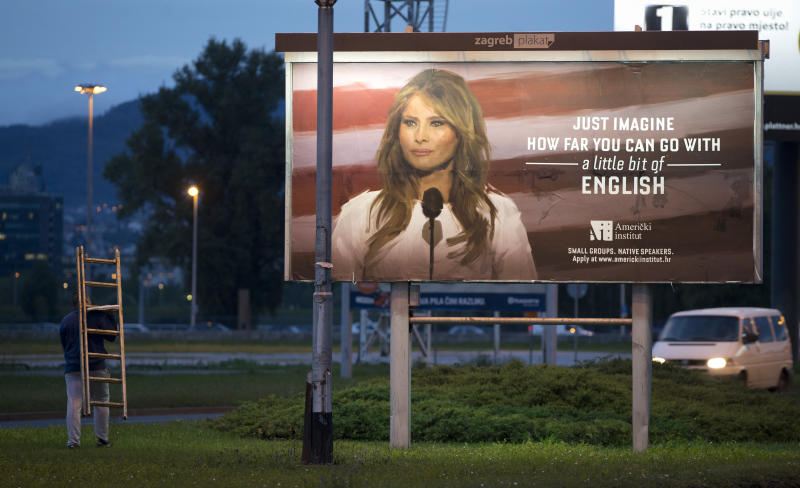 A worker carrying a ladder walks past a billboard depicting the first lady Melania Trump and advertising a language school displayed in Zagreb, Croatia, Friday, Sept. 15, 2017. (AP Photo/Darko Bandic)