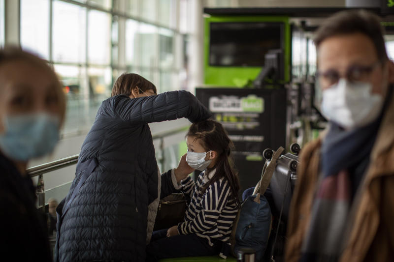 A woman fixes a mask to a child at Barcelona airport, Spain, Thursday, March 12, 2020. (Emilio Morenatti/AP)