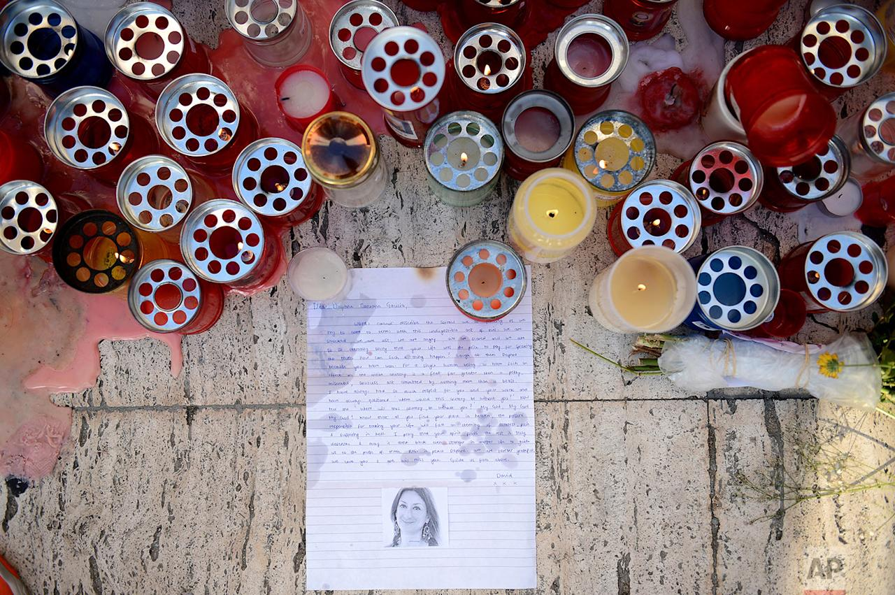<p>Candles, notes and paper cuttings lie next to the Love Monument in St. Julian, Malta, the day after the killing of journalist Daphne Caruana Galizia. The Maltese investigative journalist who exposed the island nation's links to offshore tax havens through the leaked Panama Papers was killed Monday when a bomb exploded in her car. (AP Photo/ Rene Rossignaud) </p>