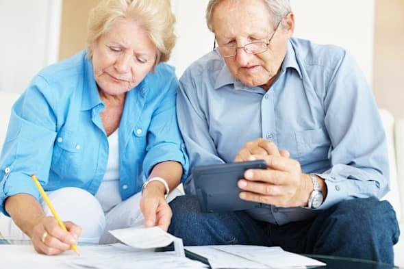 Portrait of a retired senior couple calculating their personal finances at home