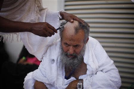 A Muslim pilgrim has his head shaved after casting pebbles at a pillar that symbolizes Satan during the annual haj pilgrimage, on the first day of Eid al-Adha in Mina, near the holy city of Mecca October 15, 2013. REUTERS/Ibraheem Abu Mustafa