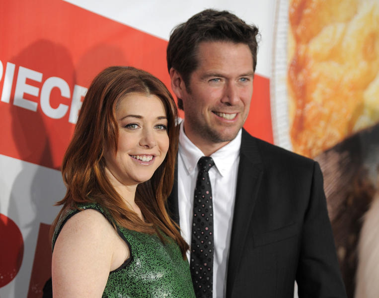 """FILE - This March 19, 2012 file photo shows actress Alyson Hannigan, a cast member in """"American Reunion,"""" posing with her husband, actor Alexis Denisof, at the premiere of the film in Los Angeles. Hannigan obtained a temporary restraining order on Wednesday, Feb. 13, 2013 claiming a New Hampshire man recently released from a mental institution has been threatening to kill her and harm her family in online postings. (AP Photo/Chris Pizzello, file)"""
