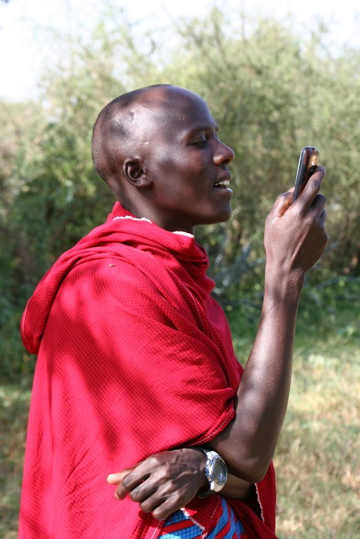 A man in traditional Maasai dress holds a phone up to look at it.