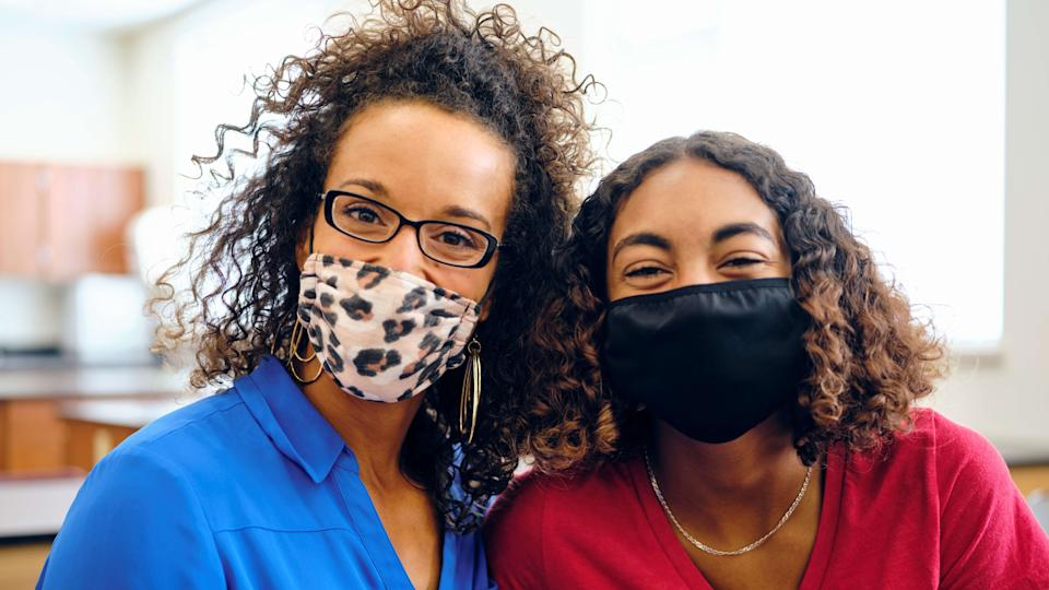 High school student and teacher in a classroom, wearing protective face masks to help against spreading infectious disease.
