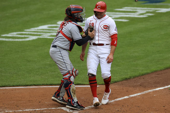 Cleveland Indians' Austin Hedges, left, tags out Cincinnati Reds' Joey Votto at home plate during the fifth inning of a baseball game in Cincinnati, Saturday, April 17, 2021. (AP Photo/Aaron Doster)