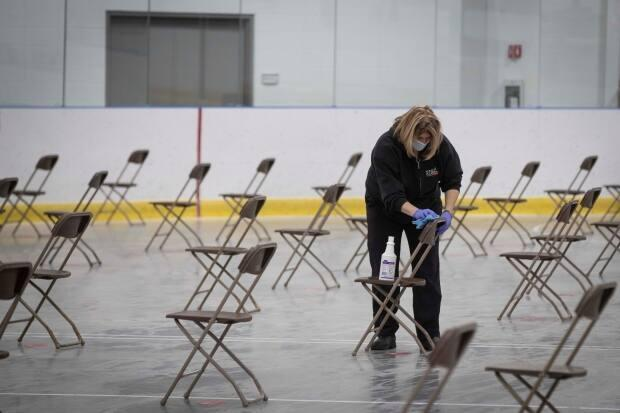 Audra Wash cleans chairs at the waiting area at the Invista Centre in Kingston, Ont., on March 1, 2021. The centre is being used as a COVID-19 vaccination site for the KLF&A health unit. (Lars Hagberg/Canadian Press - image credit)