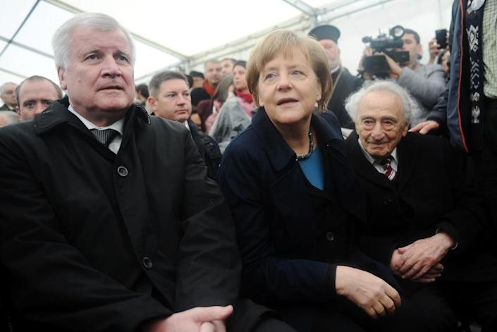 Bavarian leader Horst Seehofer (left), German Chancellor Angela Merkel and Holocaust survivor Max Mannheimer wait for the start of a ceremony to mark 70 years since the Nazi camp of Dachau was liberated by US forces, during a ceremony on May 3, 2015 (AFP Photo/Andreas Gebert)