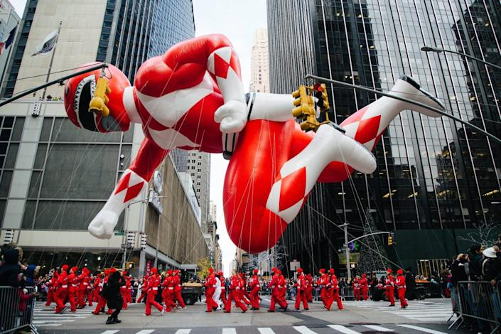 Amid skyscrapers, a Power Ranger balloon floats, dwarfing parade participants on the street.