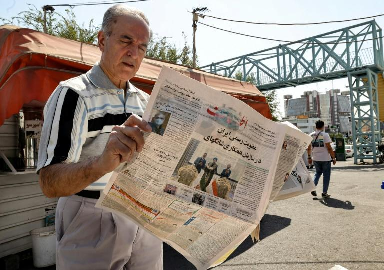 """An Iranian man reads a copy of the daily newspaper """"Etalaat"""" headlined, """"Iran is a new member of the Shanghai Cooperation Organisation"""", at a kiosk in Tehran on September 18, 2021 (AFP/ATTA KENARE)"""