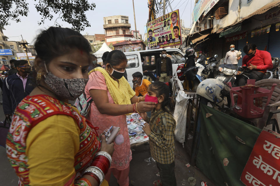 A woman puts on a face mask on her daughter at a market place in New Delhi, India, Thursday, Nov. 19, 2020. India's total number of coronavirus cases since the pandemic began has crossed 9 million. Nevertheless the country's new daily cases have seen a steady decline for weeks now and the total number of cases represents 0.6% of India's 1.3 billion population. (AP Photo/Manish Swarup)