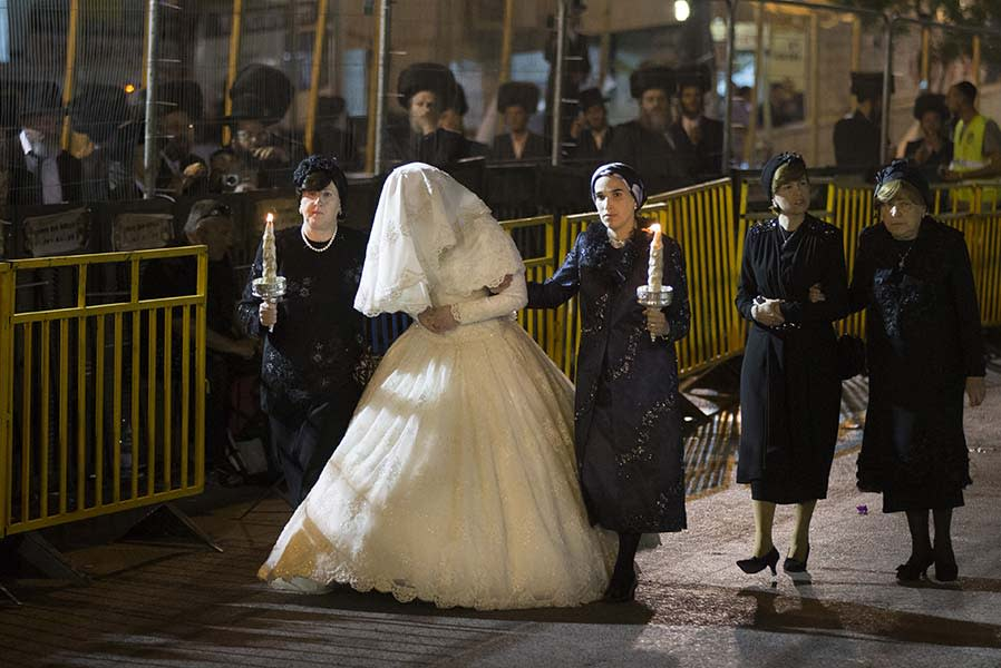 "<div class=""caption-credit""> Photo by: Getty Images</div><div class=""caption-title""></div>The 19-year-old bride, Hannah Batya Penet, wore a traditional white wedding dress made of lace and encrusted with pearls and crystals. Female relatives led her into the ceremony."