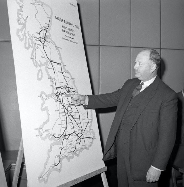 Richard Beeching looking at a large map, showing how British Rail trunk routes might look in 1984  (PA)