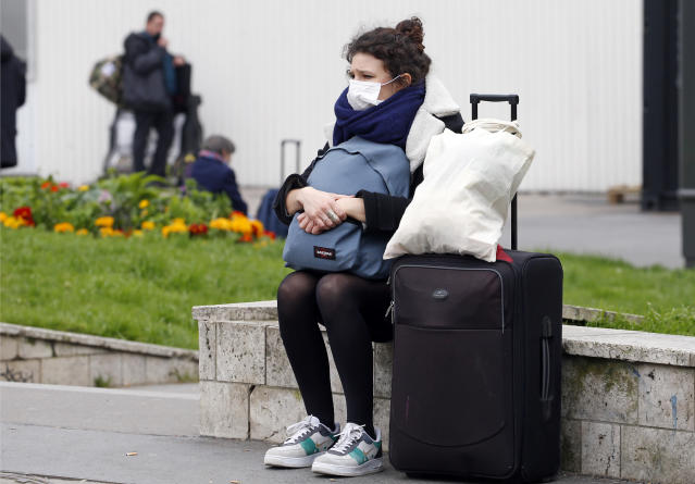 A masked passenger is pictured waiting for a train at Montparnasse station, Paris, on 17 March. France has had more than 6,600 confirmed cases. (Getty Images)