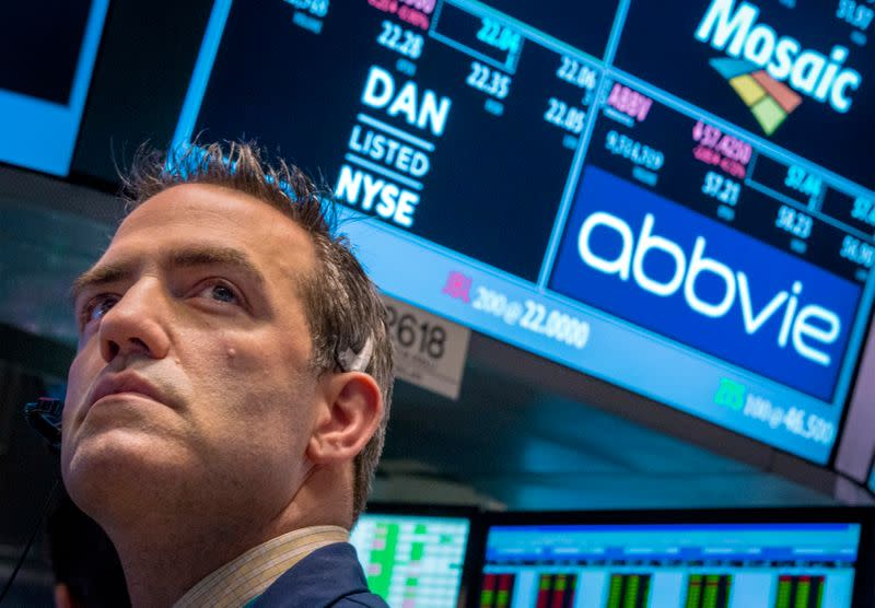 FILE PHOTO: A trader works by the post that trades AbbVie on the floor of the New York Stock Exchange