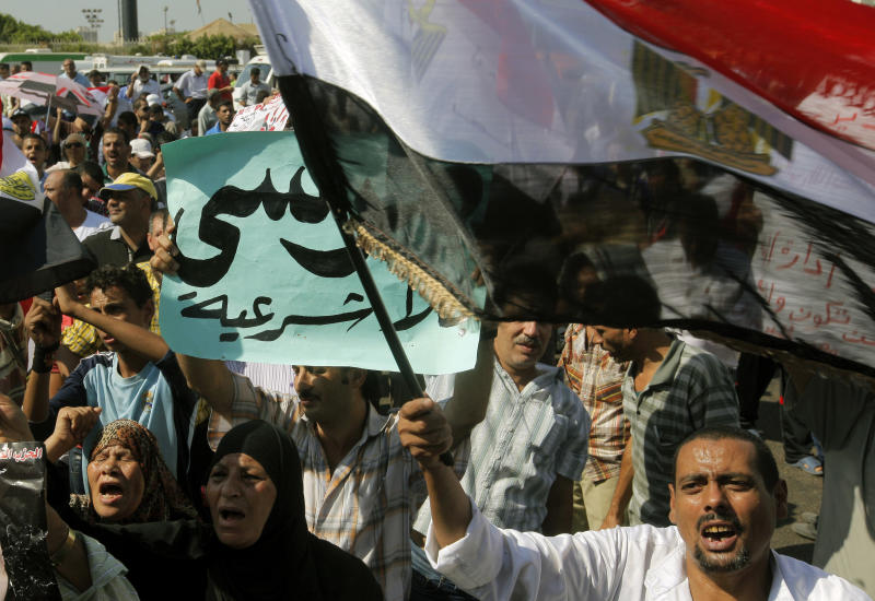 "Egyptian anti-Muslim Brotherhood protesters shout slogans during a rally to denounce the country's Islamist President Mohammed Morsi and his Muslim Brotherhood group in Cairo, Egypt Friday, Aug. 24, 2012.  Friday's protests were the first attempt by Morsi's opponents to stage a major demonstration against the new president. Arabic reads "" Morsi is illegal.""  (AP Photo/Amr Nabil)"