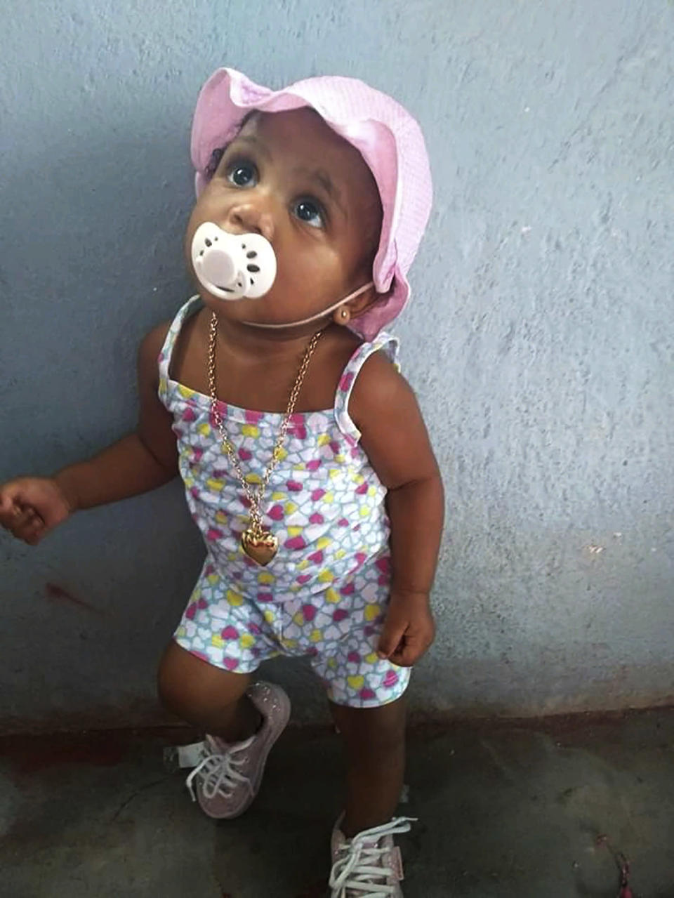 In this Feb. 10, 2020, photo, provided by Andréa de Sousa, her daughter Vitoria Gabrielle looks up while leaning against a wall, in Rio de Janeiro, Brazil. The girl with a constant smile celebrated her first birthday in February, but after recovering from viral meningitis, Vitoria Gabrielle suffered gastrointestinal problems that sent her from her mother's barely furnished hilltop home back to the hospital several times for treatment. It was during an April hospital stay that de Sousa suspects her daughter was infected with the coronavirus that was just starting to circulate in Rio and Brazil. Vitoria Gabrielle died in June. (Courtesy of Andréa de Sousa via AP)