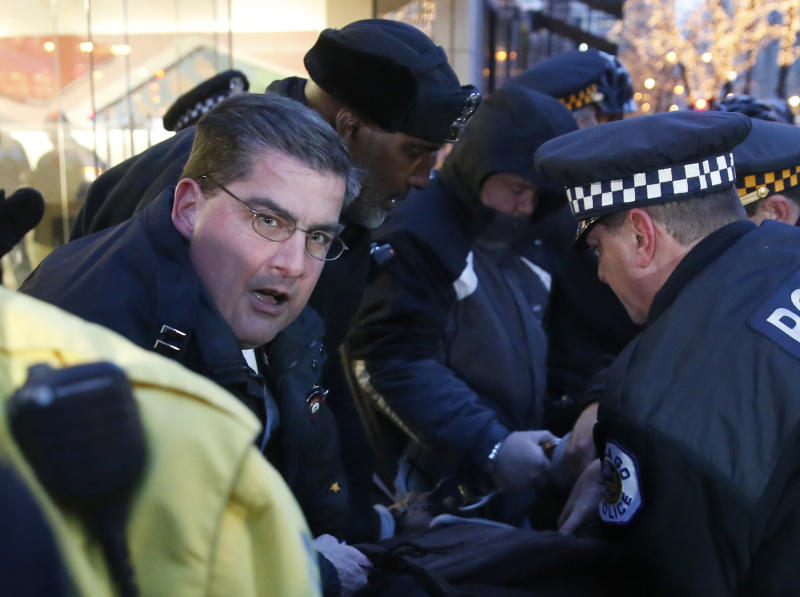 In this Feb. 23, 2016 photo, then Chicago police Capt. Paul Bauer, left, takes part in the arrest of a protester outside an Apple store on Magnificent Mile in Chicago. Promoted to commander, Bauer, 53, a 31-year veteran of the department, was fatally shot Tuesday, Feb. 13, 2018, in downtown Chicago after he spotted a man matching the radio description of an armed suspect officers were chasing on foot, the city's police superintendent said. (AP Photo/Charles Rex Arbogast)