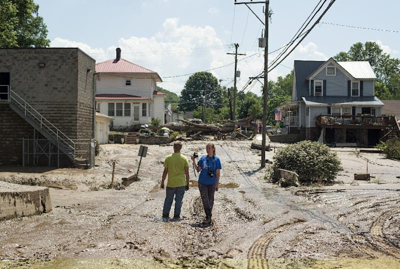 People stand in the middle of a mud covered street left over from the flooding of the Elk River in Clendenin, West Virginia (AFP Photo/Ty Wright)