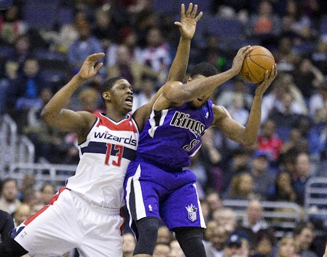 Washington Wizards center Kevin Seraphin (13) fights with Sacramento Kings small forward Rudy Gay (8) for a rebound during the first half of an NBA basketball game, Sunday, Feb. 9, 2014, in Washington. (AP Photo/ Evan Vucci)