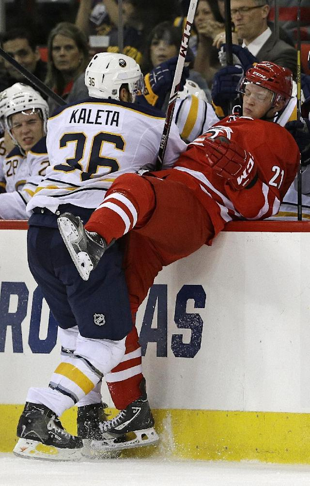 Carolina Hurricanes' Drayson Bowman (21) is checked by Buffalo Sabres' Patrick Kaleta (36) during the first period of an NHL preseason hockey game on Friday, Sept. 27, 2013, in Raleigh, N.C. (AP Photo/Gerry Broome)