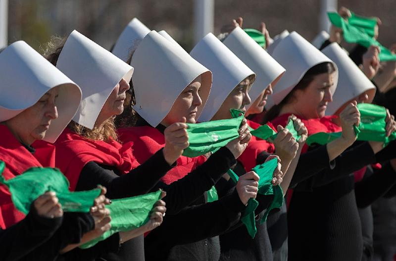 """Activists in favor of the legalization of abortion disguised as characters from Canadian author Margaret Atwood's feminist dystopian novel """"The Handmaid's Tale"""" display green headscarves in Buenos Aires, on August 5, 2018 (AFP Photo/ALEJANDRO PAGNI)"""