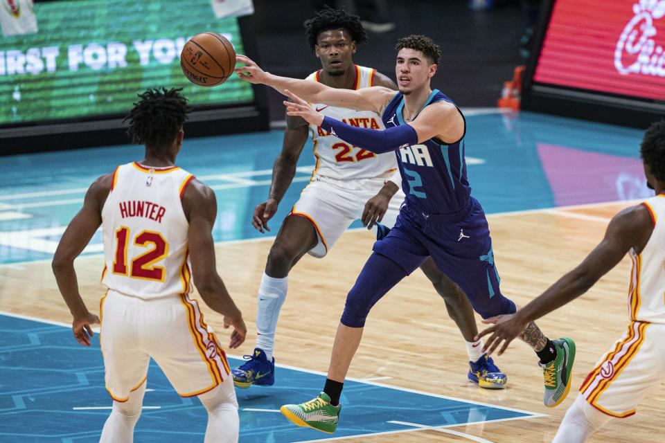 FILE - In this Jan. 9, 2021, file photo, Charlotte Hornets guard LaMelo Ball (2) looks away while passing the ball past Atlanta Hawks forward De'Andre Hunter (12) and forward Cam Reddish (22) during the first half of an NBA basketball game in Charlotte, N.C. Balls versatility as a passer, scorer and rebounder earned him NBA Rookie of the Year honors Wednesday, June 16, despite his missing 21 games with a fractured wrist. Ball beat out finalists Anthony Edwards from the Minnesota Timberwolves and Tyrese Haliburton from the Sacramento Kings to win the award, which was determined by a global panel of 100 writers and broadcasters who cover the league. (AP Photo/Jacob Kupferman, File)