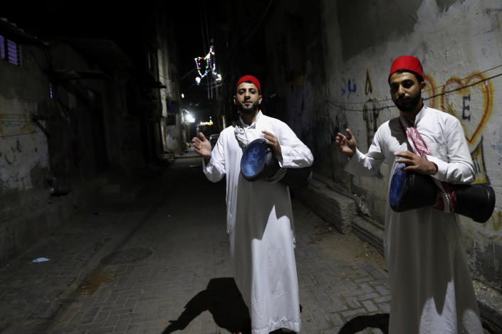 Hamodah Zakout, left, and his brother Ahmad, right, Palestinian awakener, or Al Musaharati in Arabic, beat drums to wake up Muslims for their late night suhur meal before they start the last day fasting of the holy month of Ramadan, along the alleys early Wednesday at Shati refugee camp, in Gaza City, April 21, 2021. Muslims across the world are observing the holy fasting month of Ramadan, where they refrain from eating, drinking and smoking from dawn to dusk. (AP Photo/Adel Hana)