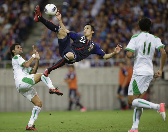 Japan's Maya Yoshida (C) shoots the ball between Iraq's Waleed Salim (L) and Amjed Radhi Yousuf Al-Janabi during their 2014 World Cup qualification soccer match in Saitama, north of Tokyo, September 11, 2012. REUTERS/Toru Hanai (JAPAN - Tags: SPORT SOCCER)