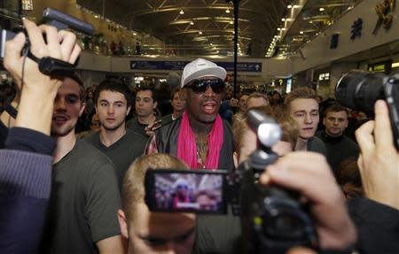 Former NBA basketball player Dennis Rodman talks to journalists as he arrives at the Beijing Capital International Airport to leave for Pyongyang, in Beijing, January 6, 2014. REUTERS/Jason Lee