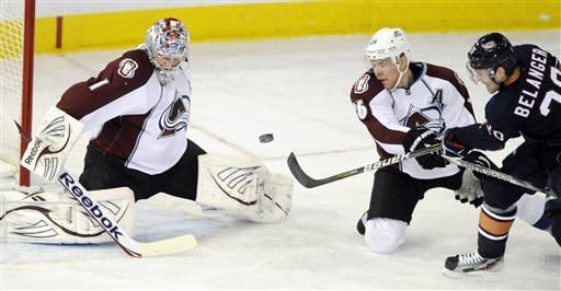 Edmonton Oilers' Eric Belanger, right, shoots past Colorado Avalanche's Paul Stastny as goalie Semyon Varlamov, left, makes the save during the first period of an NHL hockey game, Tuesday, Jan. 31, 2012, in Edmonton, Alberta. (AP Photo/The Canadian Press, John Ulan)