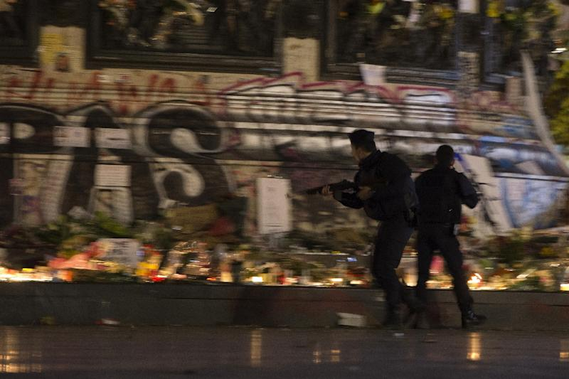 Armed police respond as panic spreads at the Place de la Republique in Paris November 15, 2015, where firecrackers alarmed a crowd gathered to mourn those killed in the November 13 jihadist attacks (AFP Photo/Joel Saget)