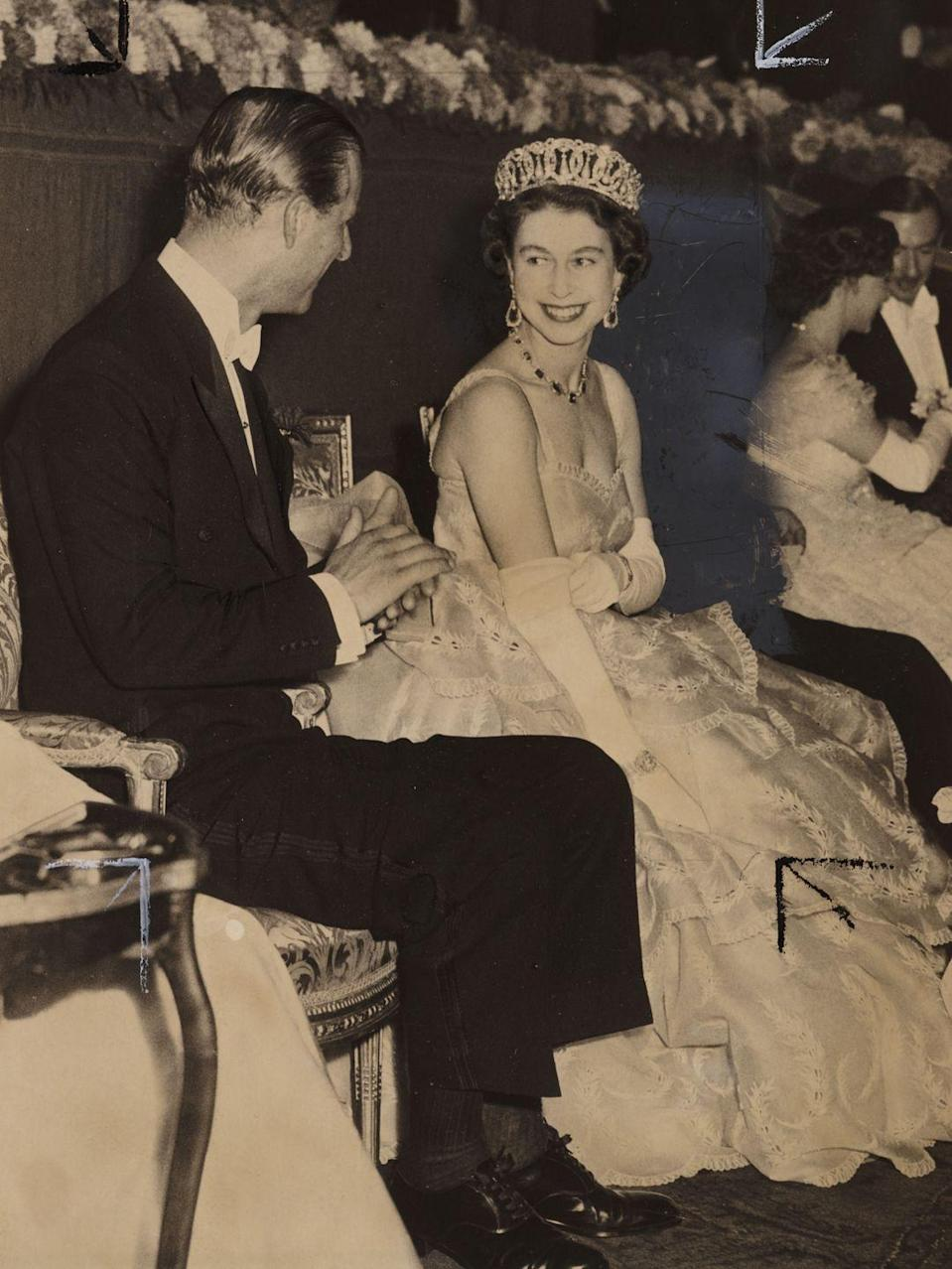 <p>Queen Elizabeth and Prince Philip share a smile at the Royal Film Show in 1953. The Royal couple and the other audience members saw Walt Disney's Rob Roy.<br> </p>