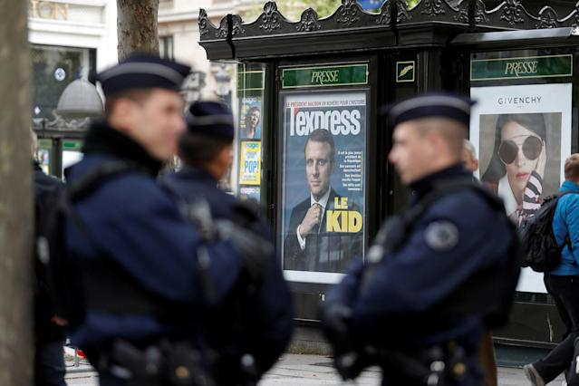 <p>French police stand near a newsstand with a magazine cover showing French president-elect Emmanuel Macron, on the Champs Elysees in Paris, May 8, 2017. (Eric Gaillard/Reuters) </p>