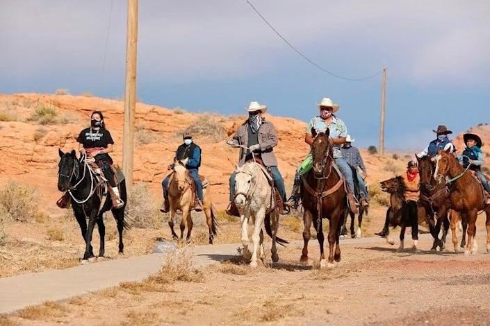 Allie Young, left, a Diné woman on the Navajo Nation in Arizona, is among a group of Native Americans as they ride on horseback to the polls on Election Day (AP)