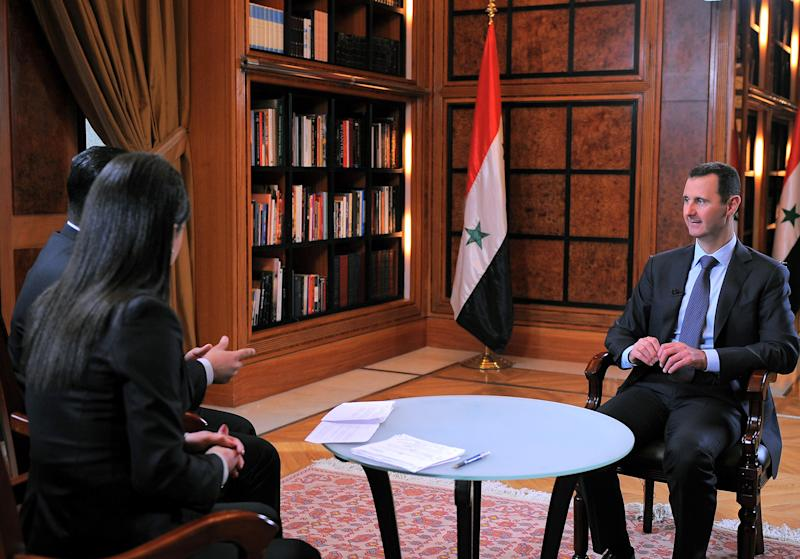 "This photo released by the Syrian official news agency SANA on Wednesday, April 17, 2013, shows Syrian President Bashar Assad, right, during an interview broadcast on Syrian state television in Damascus, Syria. Syria's president accused the West on Wednesday of backing al-Qaida in his country's civil war, warning it will pay a price ""in the heart"" of Europe and the United States as the terror network becomes emboldened. Bashar Assad also lashed out at Jordan for allowing ""thousands"" of fighters to enter Syria through its borders. The rare TV interview comes as the embattled president's military is fighting to reverse rebel advances, with a rocket attack killing at least 12 people in a central village on Wednesday. (AP Photo/SANA)"