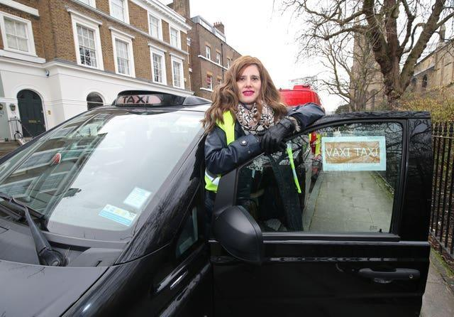 Dr Sharon Raymond, director of Covid Crisis Rescue Foundation, poses next to a Vaxi Taxi (Yui Mok/PA)