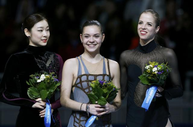 Russia's Adelina Sotnikova, Korea's Yuna Kim and Italy's Carolina Kostner stand together during the flower ceremony at the Figure Skating Women's free skating Program at the Sochi 2014 Winter Olympics, February 20, 2014. REUTERS/Alexander Demianchuk (RUSSIA - Tags: OLYMPICS SPORT FIGURE SKATING)