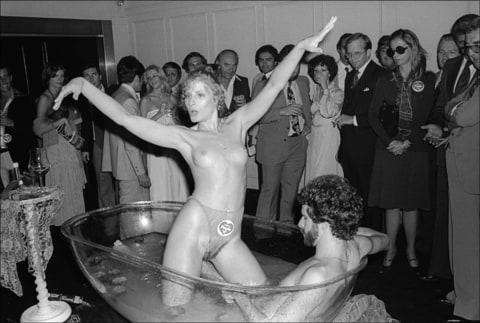 At the Purple magazine party, a mostly naked couple in a clear bathtub perform for men and women in business attire, New York, New York, September 15, 1977.